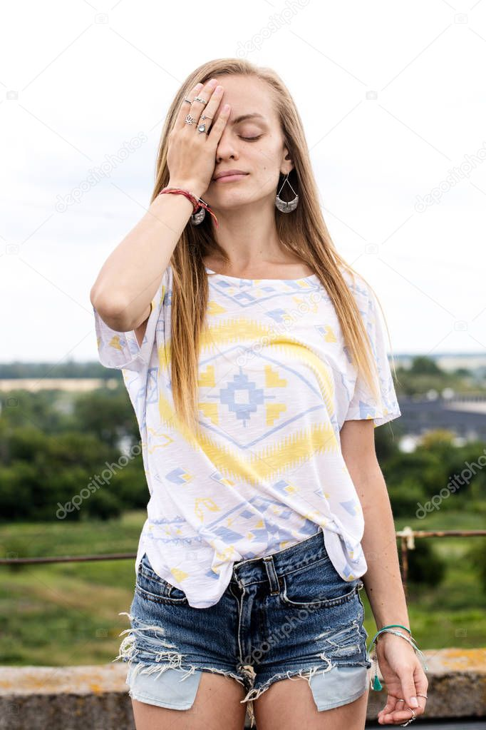 Beautiful long-haired girl with eyes closed hands