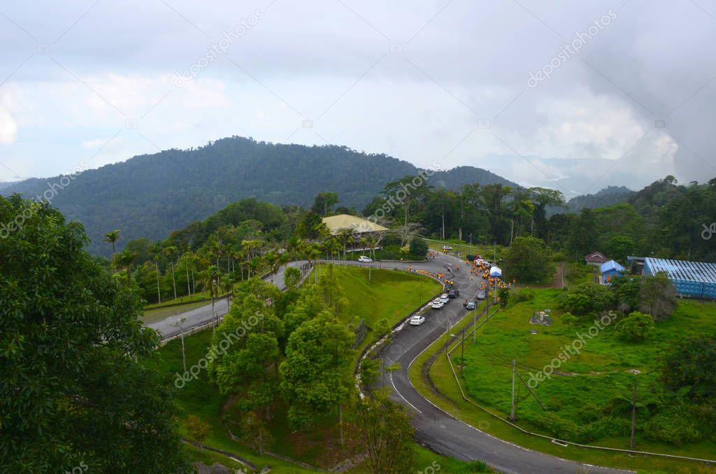 Top view from Gunung Raya mountain to winding asphalt road, Langkawi island, Malaysia. Mountain serpentine, lots of people, cars and tents. Athletes in bright orange uniforms are preparing for race.