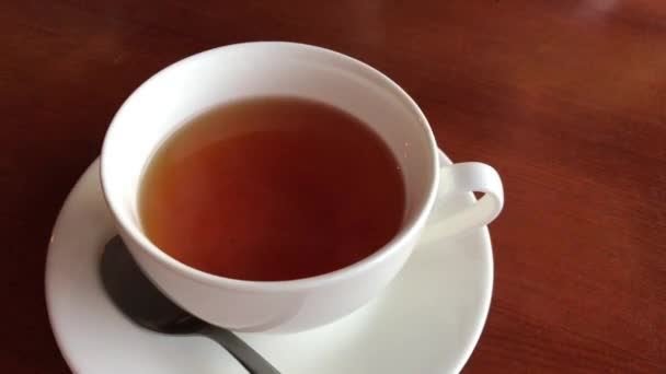 Šálek černého čaje stojí na hnědém stole, pára od horkého čaje. Bílý čaj se lžičkou