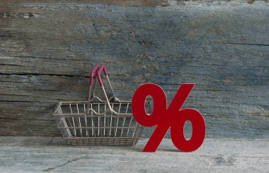 Shopping cart and sign percent with sale concept on wood background