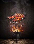 Gril konvici s horkou brikety, litinovým roštem a chutné špejle létání ve vzduchu