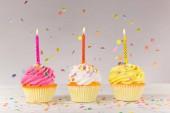Színes születésnapi kupa sütemények, fából készült háttér