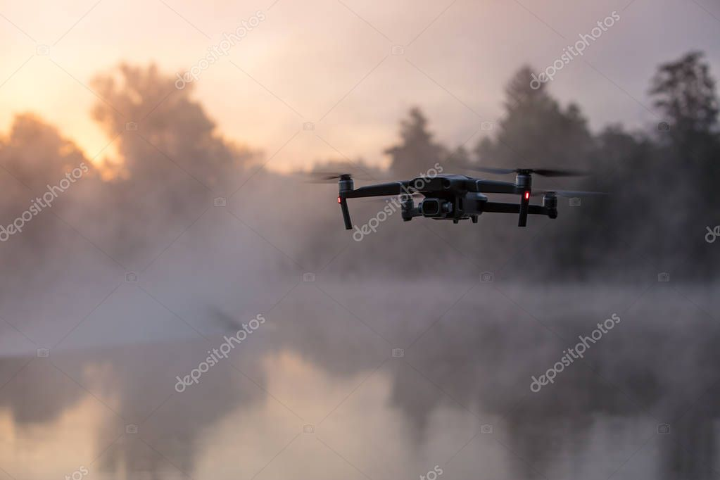Drone copter with digital camera, river with fog on background. Modern technology, UAV concept.