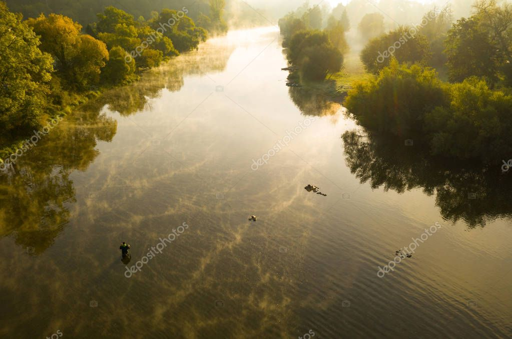 Aerial shot of a man fly fishing in a river with a fog during summer morning.