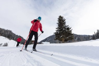 Man cross-country skiing during sunny winter day.