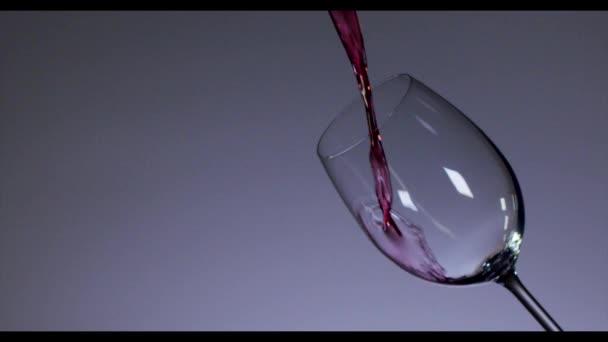 Červené víno nalil do sklenice na víno přes tmavé pozadí. 4k, pomalý pohyb.