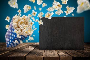 Popcorn explosion on old wooden table, close-up. stock vector