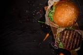 Pohled shora na chutné hamburgery na dřevěný stůl.