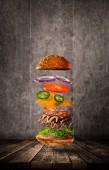 Chutný hamburger s létáním ingredience na tmavém pozadí