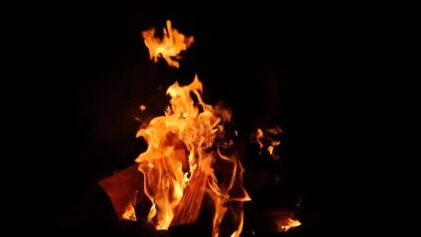 Detail z hořící oheň, plameny hořící na černém pozadí, pomalý pohyb