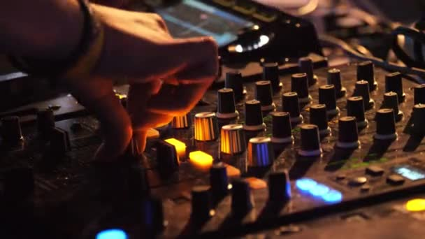 Hands of DJ plays music mixing and scratching, close-up.