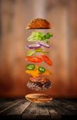 Chutné cheeseburger s létáním ingredience na tmavém pozadí