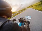 Motorkář na vysokohorské dálnici, výhled na řídítka, Dolomity, Evropa.