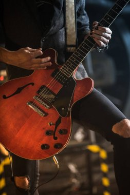 Guitarist play electricity guitar on concert stage