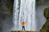 Mann bewundert die Schönheit des ikonischen Skogafoss-Wasserfalls in Island