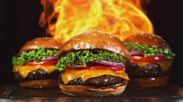 Chutný cheeseburger, ležící na staré dřevěné řezací desce s ohněm v pozadí. Super zpomalený pohyb