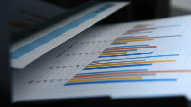 Zpráva obchodní a investiční grafy tisknout na tiskárně v kanceláři. Detailní záběr