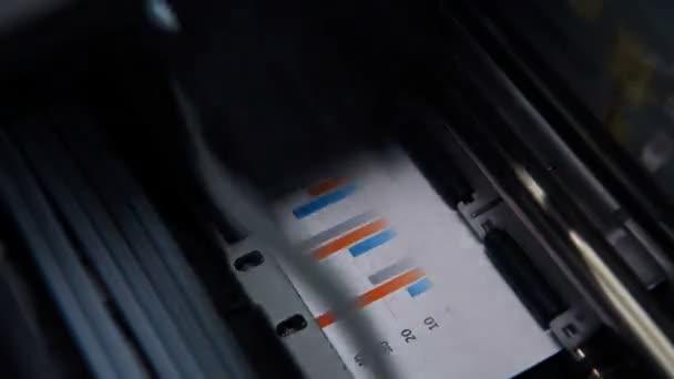 Tiskárna tiskne Business Report a investiční grafy. Finanční a obchodní koncepce