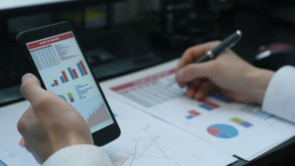 Obchodník s používáním mobilního telefonu s údaji o akciovém trhu. Údaje o ekonomické analýze v grafu. Efekt pomalého pohybu.