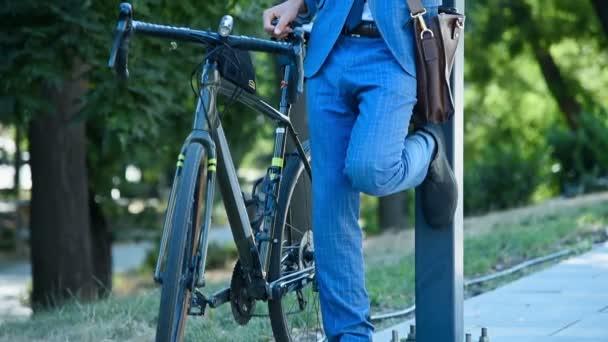 Mladý podnikatel mluví po telefonu s Bike At City Street. Koncepce obchodního a městského stylu