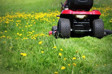Tractor lawn mower cutting the grass in springtime