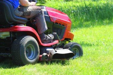 Gardener driving a riding lawn mower in a garden .