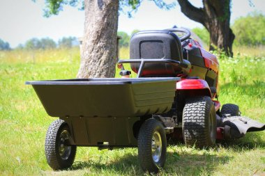 Lawn tractor mower with hitch and trailer in a garden .