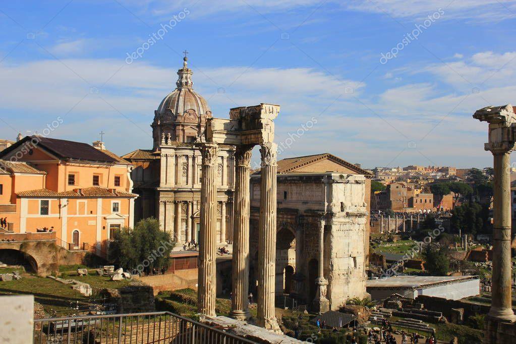 Ruins of Roman Forum. Temple of Vespasian and Titus, Arch of Septimius Severus and church of Santi Luca e Martina in Rome. Italy