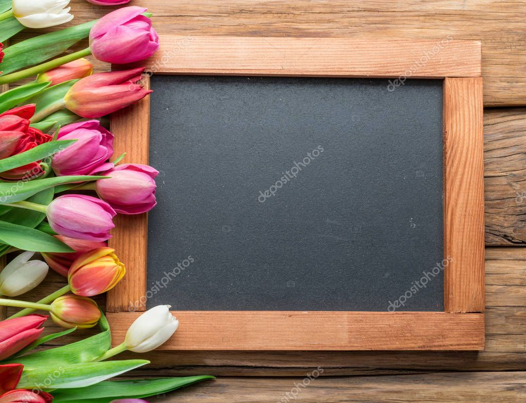 Colorful tulips arranged as frame on wooden background. Top view.