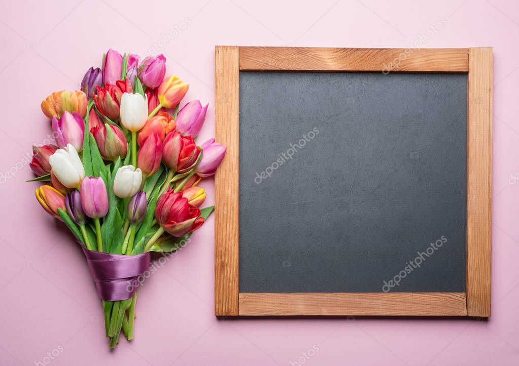 Colorful bouquet of tulips and blackboard. Spring background.