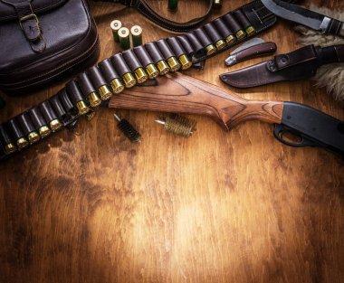 Hunting equipment - pump action shotgun, 12 guage cartridge and hunting knife.