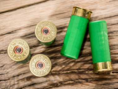 12 guage cartridge for pump shotgun on the wooden table.