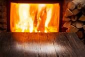 Fotografie Prázdnou dřevěný stůl a krb s teplou požáru na pozadí