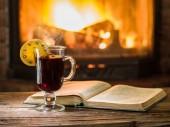 Fotografie Glühwein und ein Buch auf dem Holztisch. Kamin mit warmem Feuer im Hintergrund.