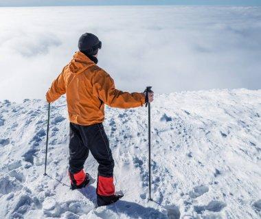 Winter hiking. Tourist on snowy mountain top enjoying beautiful view of cloudscape.