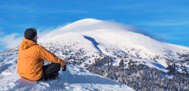 Winter hiking. Tourist on snowy mountain top enjoying beautiful view.