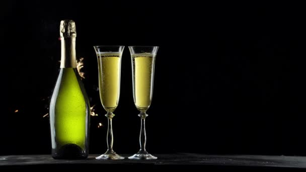 Stillleben mit einer Flasche Champagner und Gläsern. Wunderkerzen auf schwarzem Hintergrund. 4k-Video.