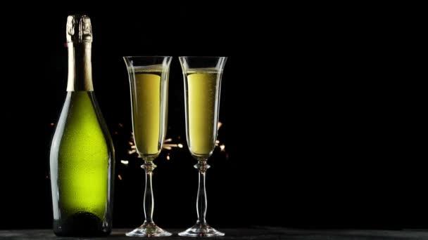 Csendélet egy üveg pezsgő és szemüveg. Csillagszórók a fekete háttér.