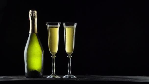 Zátiší s lahví šampaňského a brýle. Černé pozadí. 4k video.