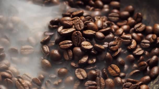 Fragrant coffee beans are roasted in a frying pan, smoke comes from coffee beans. The whole composition scrolls slowly around the camera.