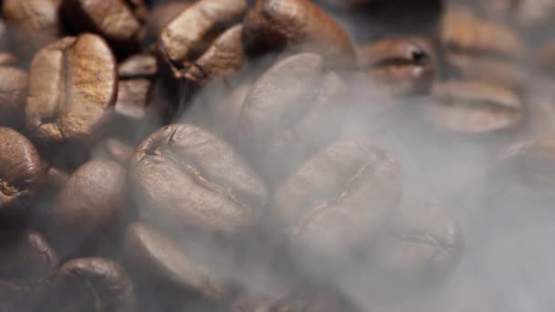 Fragrant coffee beans are roasted in a frying pan, smoke comes from coffee beans.