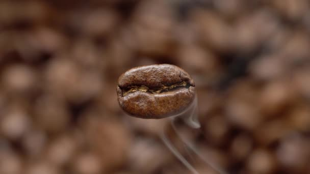 A repülő makró kávébab gőzölgő. Makro lövés. Alul van egy homályos kávé háttér.