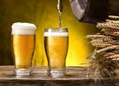 Nalil do sklenice. Sklenice piva a soudek na dřevěný stůl. Řemeslo pivovar.