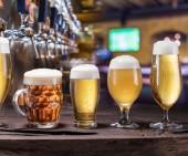 Fotografie Chlazené hrnky a sklenice piva na starý dřevěný stůl. Hospoda interiéru a barový pult s pivem kohoutů v pozadí. Sortiment piva