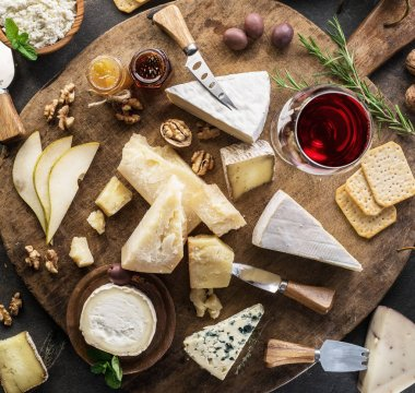 Cheese platter with different cheeses, fruits, nuts and wine on