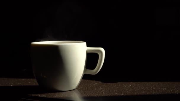 Bílý keramický šálek kávy stojí na kuchyňském stole a z ní vychází pára. Černé pozadí.