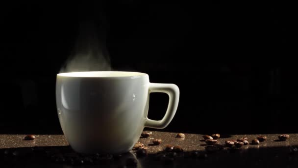 White ceramic cup of coffee stands on the kitchen table and steam comes from it. Black background.