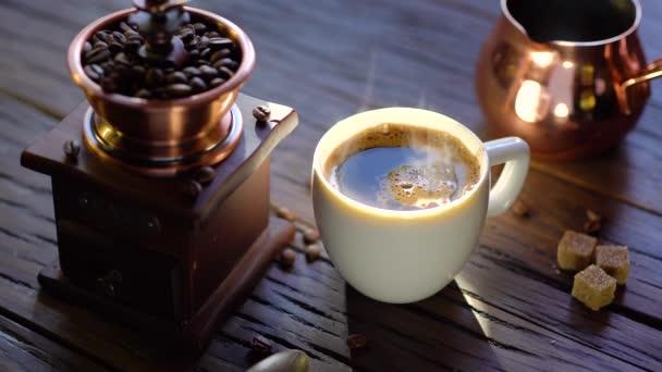 Šálek kávy s čerstvě uvařenou kávou na starém starožitném stole. Z poháru stoupá pára. Video 4k.
