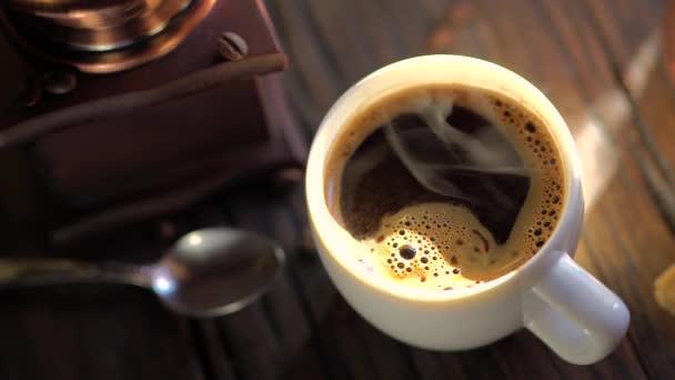 Kávés csésze frissen főzött kávéval egy régi vintage asztalon. Gőz emelkedik ki a csészéből. 4k videó.