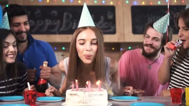 Frau bläst Geburtstagskerzen